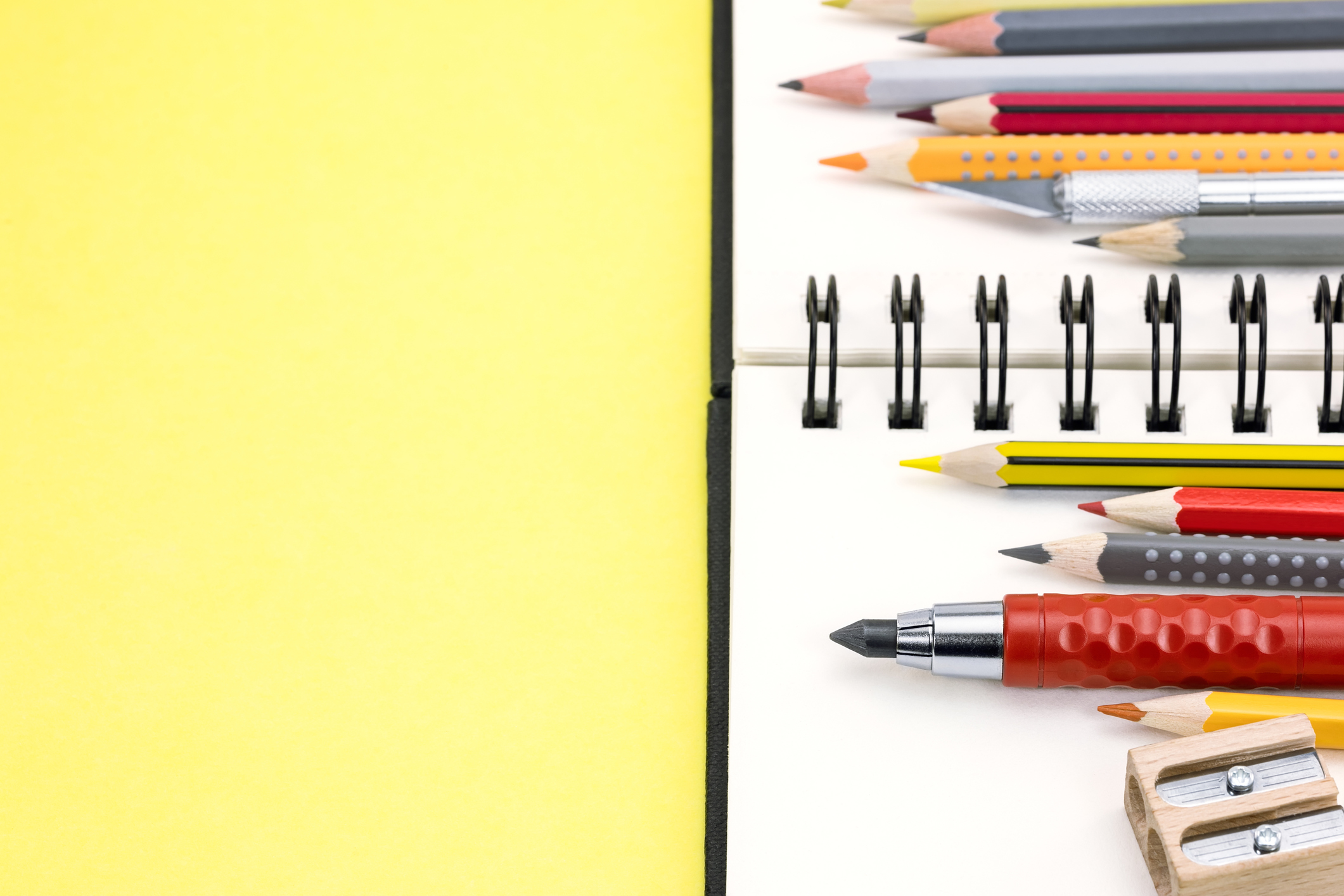 pencils of different colors and spiral notepad on yellow backgroud